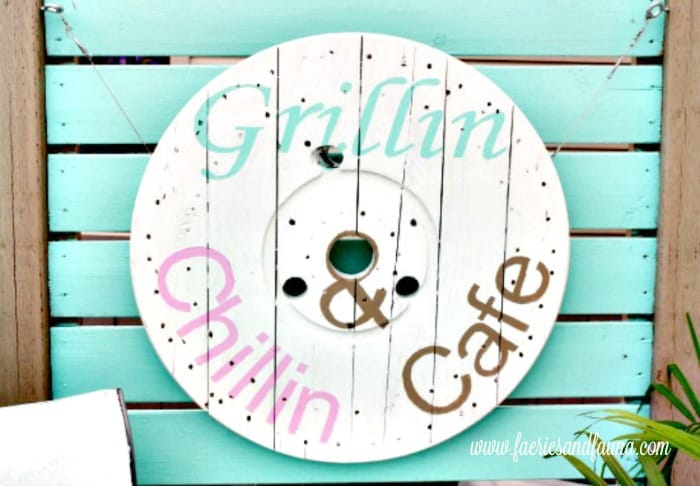 DY wooden sign made using a wooden spool. DIY backyard artwork, made from a industrial wood spool. cable Spool ideas, wood cable spool projects, large wooden spool crafts, DIY deck art, DIY deck decor