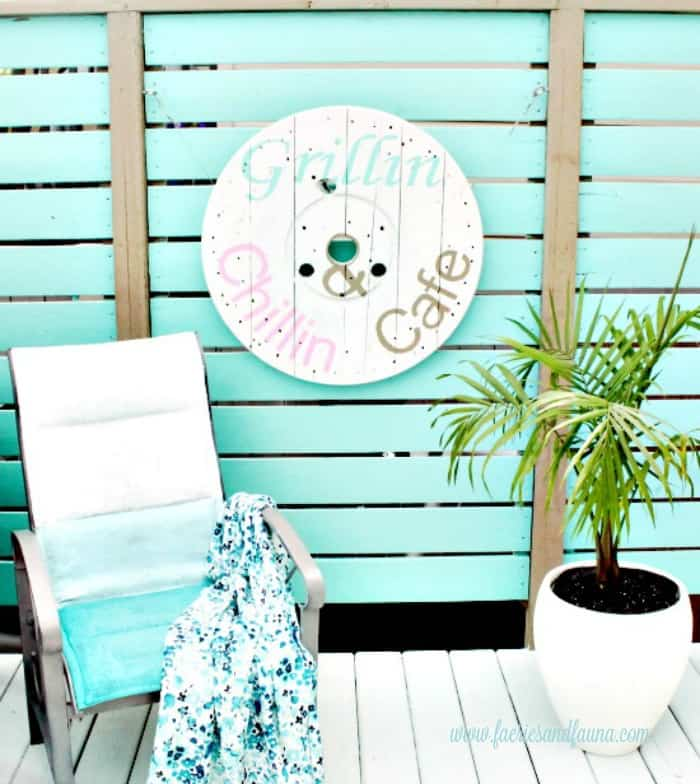 A back yard patio with a diy sign for the outside. DIY backyard artwork, made from a industrial wood spool. cable Spool ideas, wood cable spool projects, large wooden spool crafts, DIY deck art, DIY deck decor