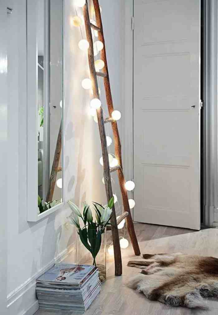 A string of globe lights cascading down a rustic ladder. A pretty fall home decor idea.