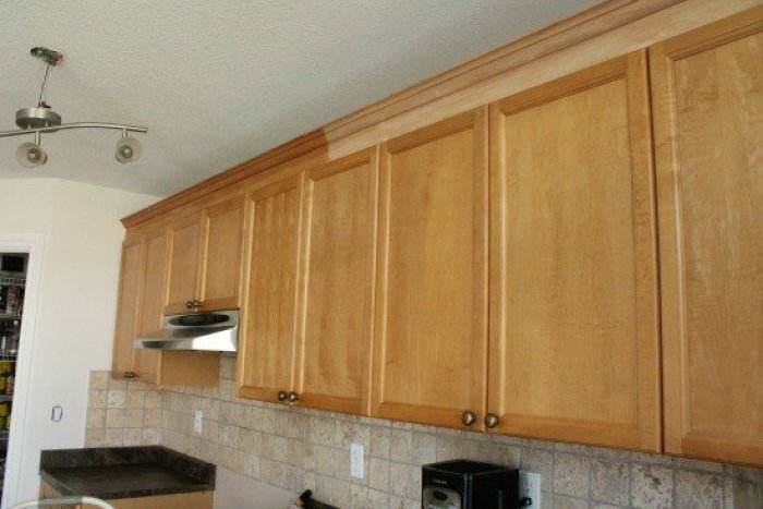 Before and after applying natural stain to oak crown moulding on existing kitchen cabinets.