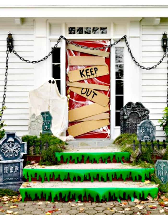 A keep out sign and graveyard decorations for a front door at Halloween. DIY Halloween front porch ideas, Halloween porch displays, DIY Halloween yard decorations, DIY Halloween front porch ideas, DIY Halloween front door decorations,