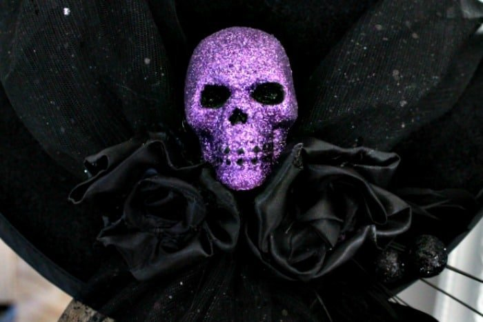 Black satin roses and a skull on the back of a DIY witches hat. DIY witch hat, witch hat decoration ideas, hat witch designs