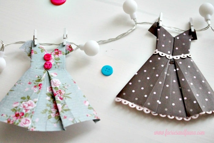Closeup of folded paper dresses decorated with buttons and lace, before being hung onto a banner. origami dress, DIY paper banner, paper dress banner, paper dress design, spring banner, DIY spring decor, paper home decor, paper dress, banner
