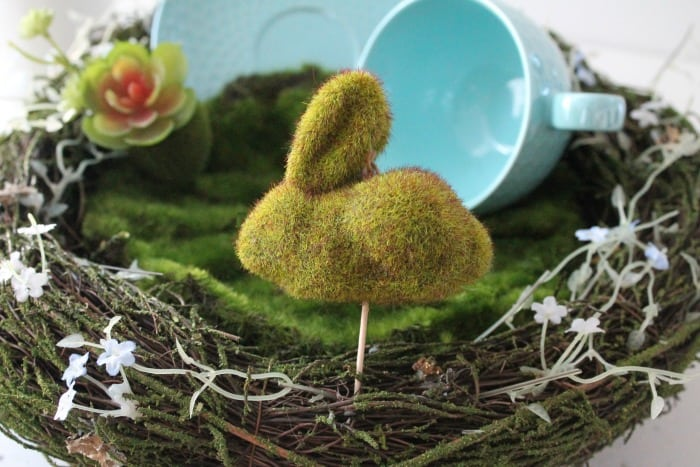 A faux moss covered miniature bunny as part of a diy fairy garden.