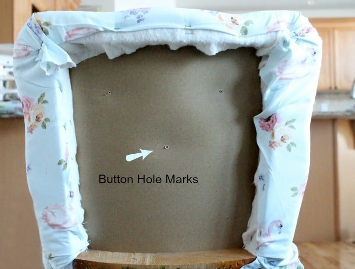 The back of an upholstered chair that has been covered in fabric and stapled in place. Chair repair, furniture restoration, recover chairs DIY, how to reupholster a chair, reupholstery, chair reupholstery, furniture repair, recovering furniture, how to recover a chair.