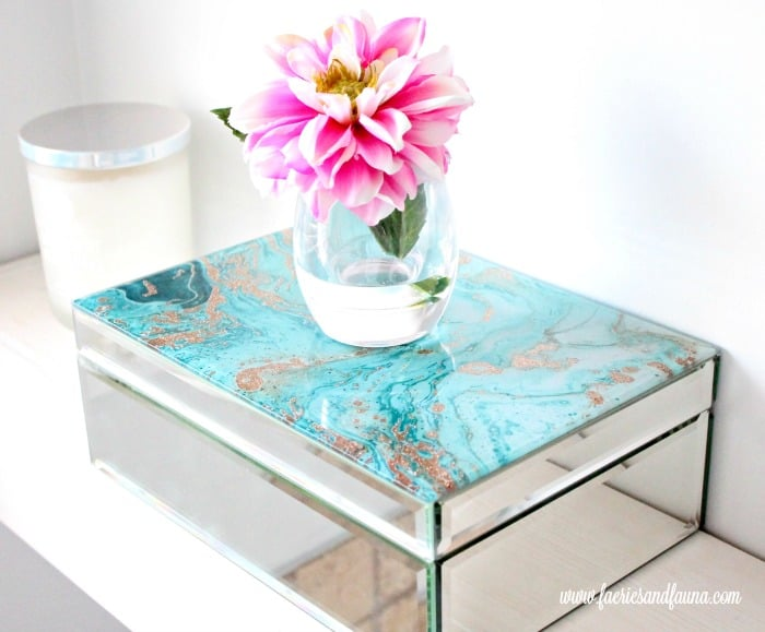 Pretty glass boxes for storage on DIY floating shelves in the bathroom.