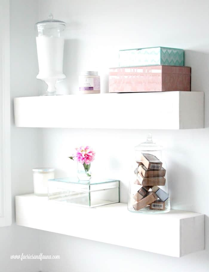 DIY floating shelves in white for bathroom organization and extra storage.