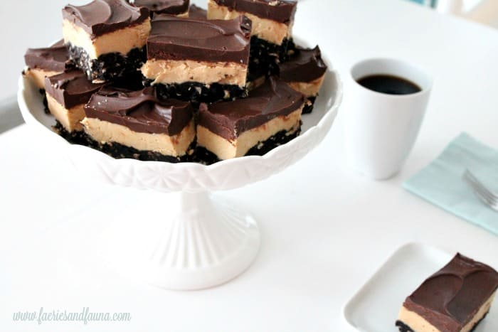 Chocolate peanut butter squares being served on a pedestal plate with coffee.