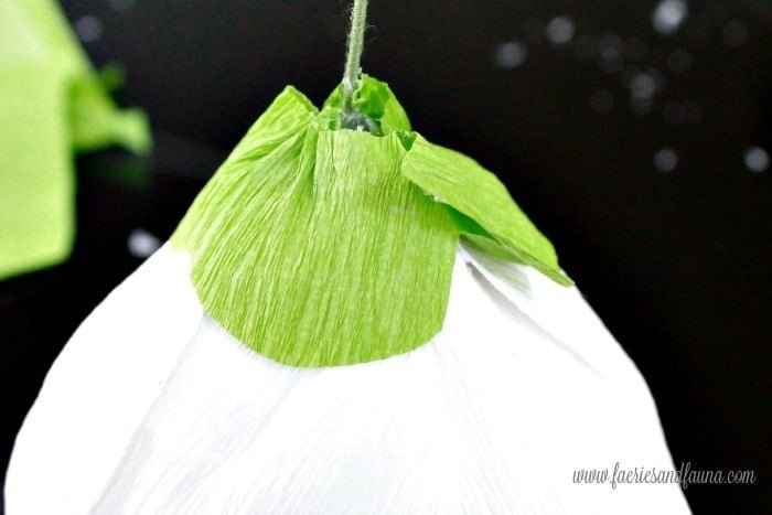 Soft green crepe paper bottom for a DIY crepe paper flower craft project. Flower making, how to make paper flowers, flower making with crepe paper, minimalist wreath, elegant wreath, diy wedding decor, paper flowers wedding, book page crafts.
