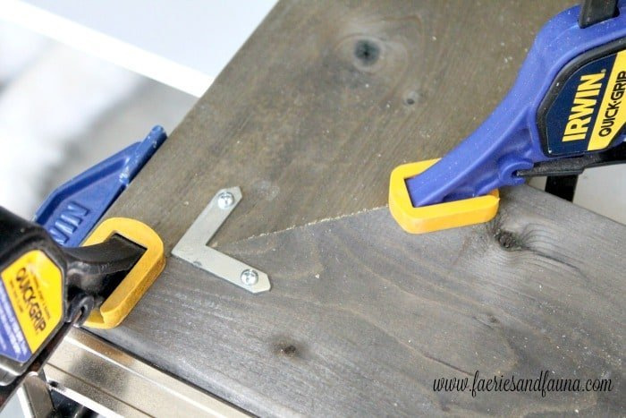 Using clamps and brackets to hold the corners of a DIY old window frame project together.