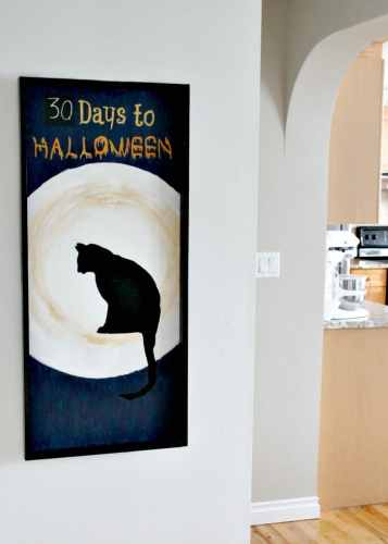 DIY Halloween Decor idea with a black cat sitting in front of the moon.