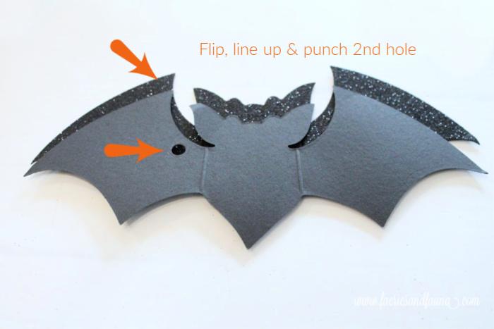 DIY Halloween Craft idea punching holes in paper bats.