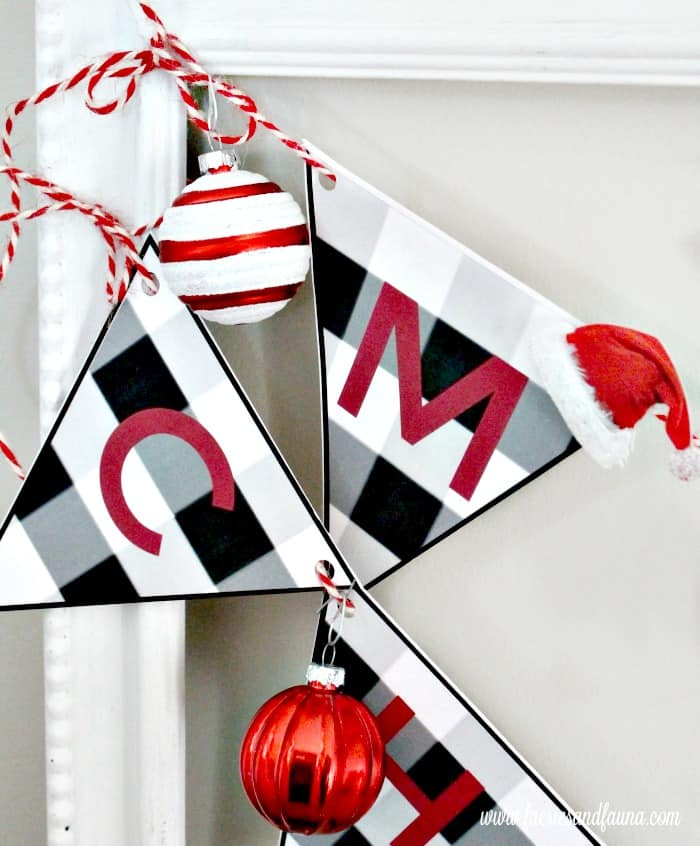 Hanging unbreakable ornaments onto an Easy Christmas craft for kids, a paper Merry Christmas banner