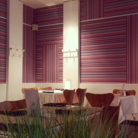 The minimalist look of the restaurant with shots of bright coloured wallpaper!