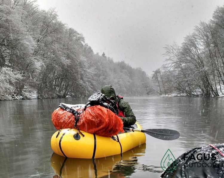 Mathias Michielsen, oprichter van Fagus Outdoor, zit in zijn packraft op Lac de Nisramont in de sneeuw