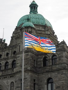 British Columbia provincial flag and dome of Legislature in Victoria
