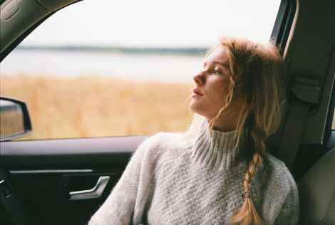 woman in sweater sitting inside a car