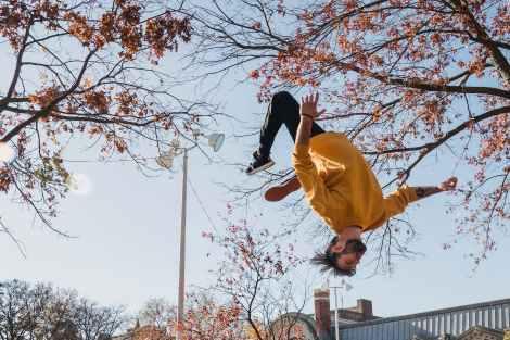 flexible man doing flip on street