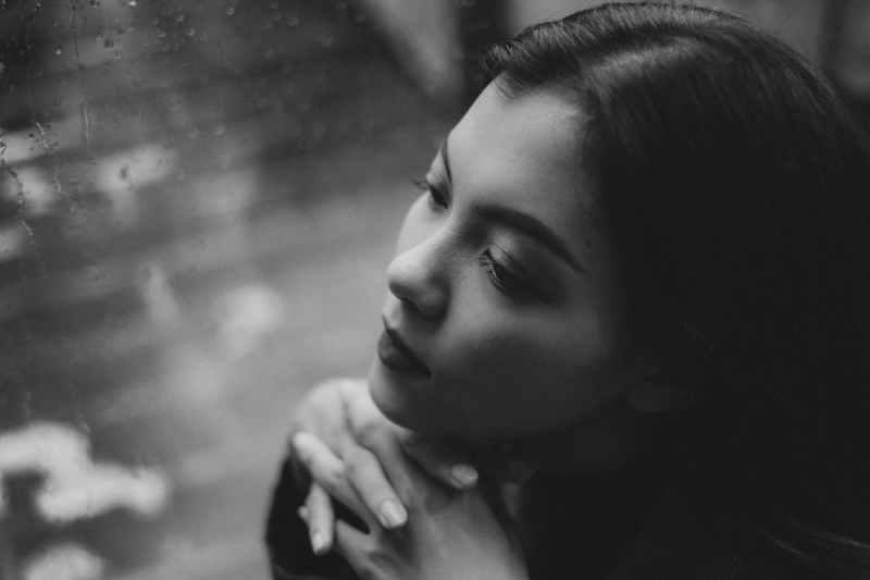 dreamy teen girl sitting near wet window