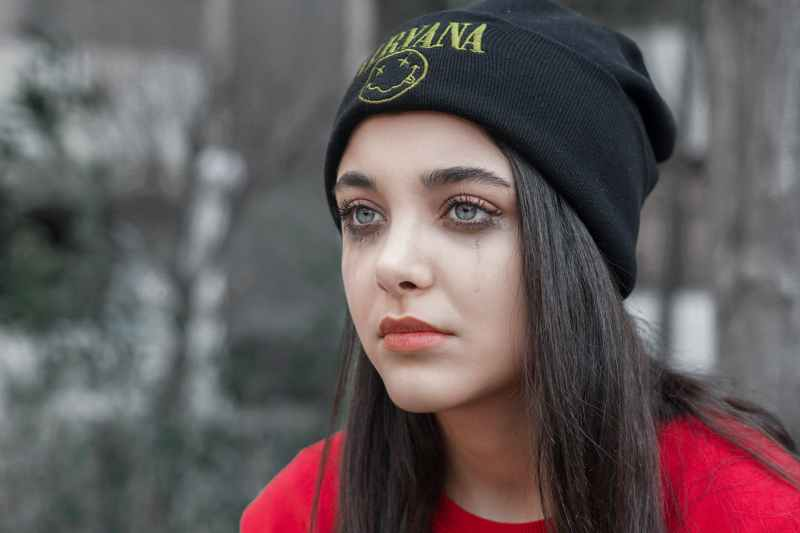 woman in black knit cap and red shirt