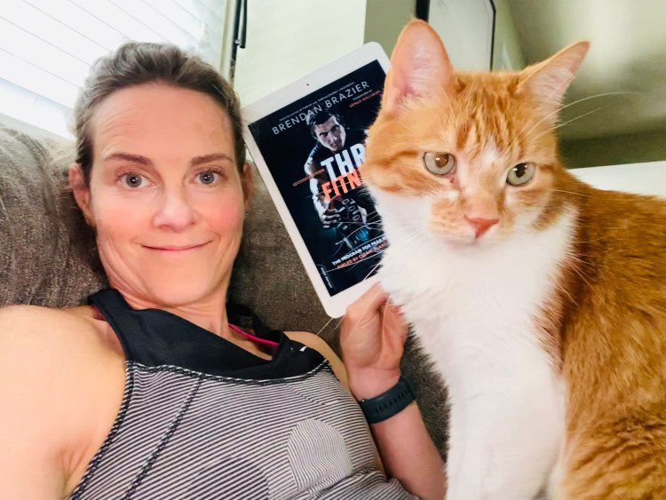 My cat and I reading Thrive Fitness.
