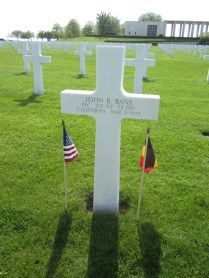 The Cemetery Commission has rubbed Omaha Beach sand in the white letters of my uncle's grave stone to highlight the letters today and placed flags there in preparation for my visit.