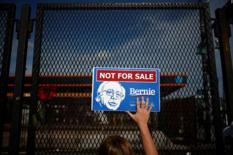 A supporter of Bernie Sanders holds a placard in protest at the perimeter walls of the Convention. REUTERS/Adrees Latif