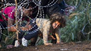refugee father and daughter crawling under barbed wire fence
