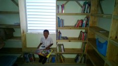 One of the Heart House kids sitting for a photo in the new library.