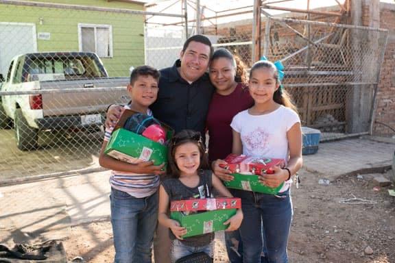 Family holding shoebox