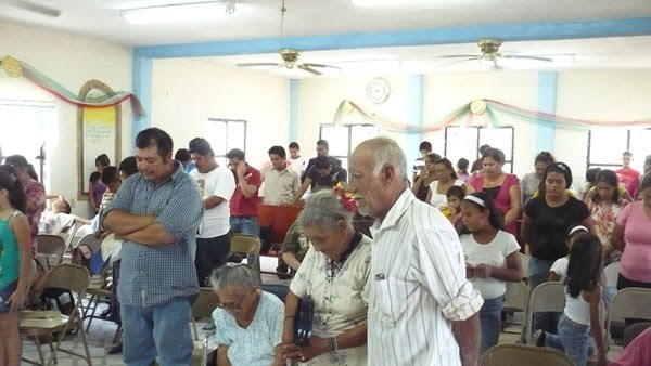 Praying at a church celebration in Miguel Aleman