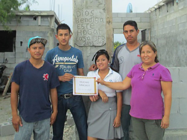 A family in Miguel Aleman in front of their new house