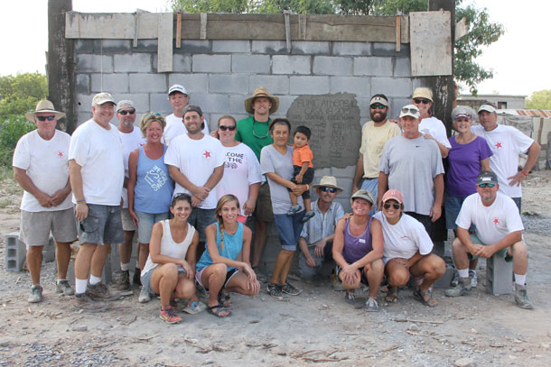 A team and a family with a completed house in Reynosa