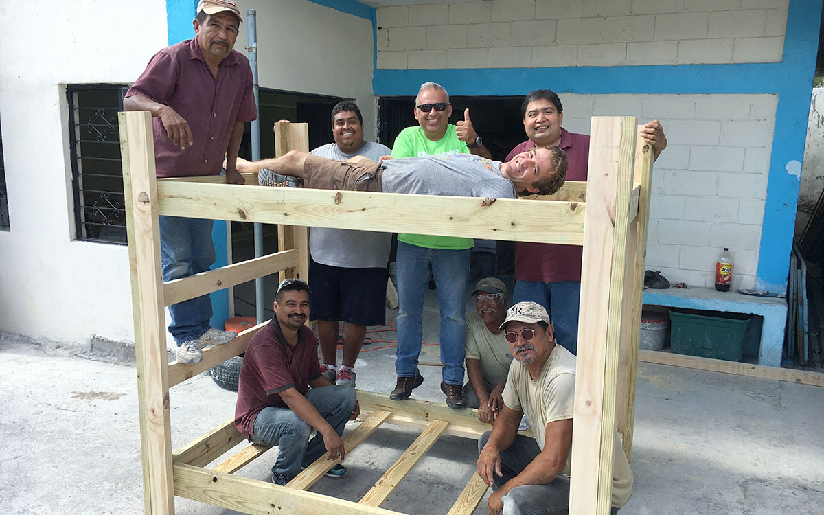 Staff in Reynosa with a newly made bunk bed in the woodworking shop