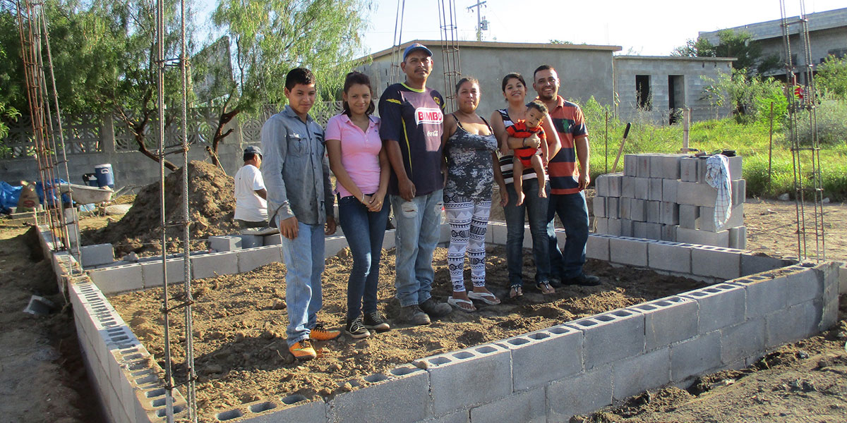 A family on the grounds of their future house in Miguel Aleman