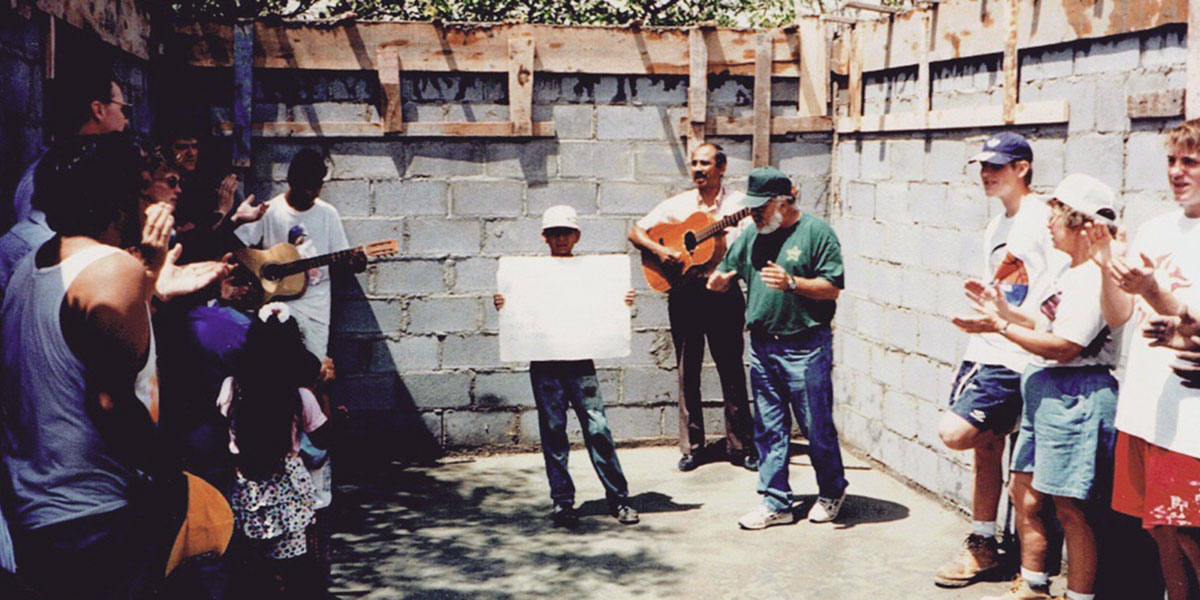 Singing songs during a devotion inside a house in 1996