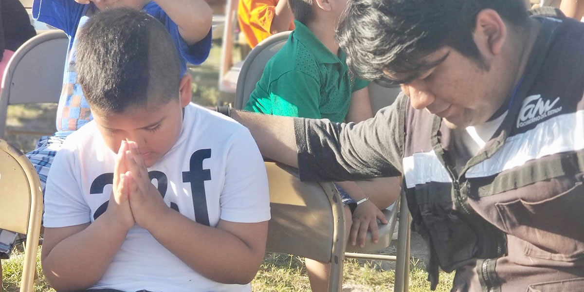 Praying together at the Childrens Day fiesta in Naranjito
