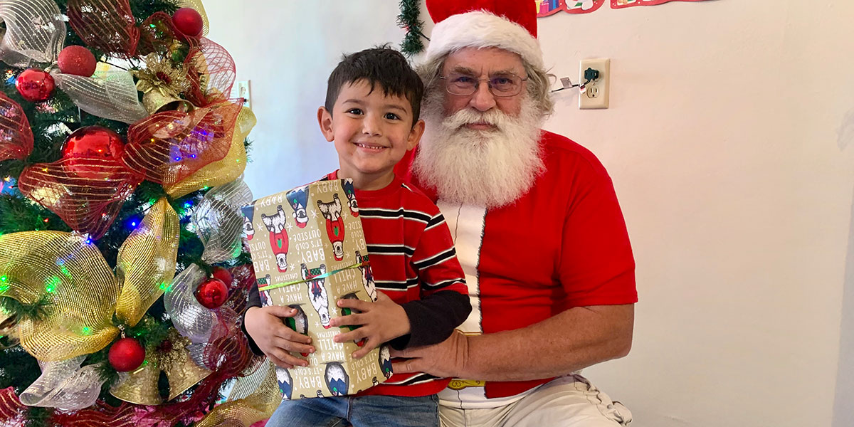 A kid with his Christmas gift and Santa at the fiesta in Miguel Aleman