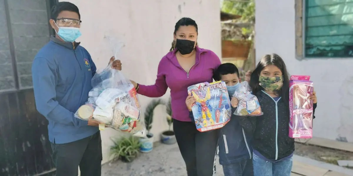 A family receiving a grocery package and toys for Christmas in Reynosa Mexico
