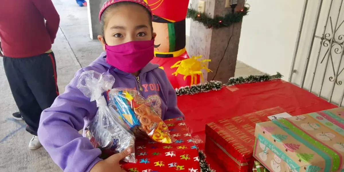 A kid receiving a gift box for Christmas in Miguel Aleman Mexico