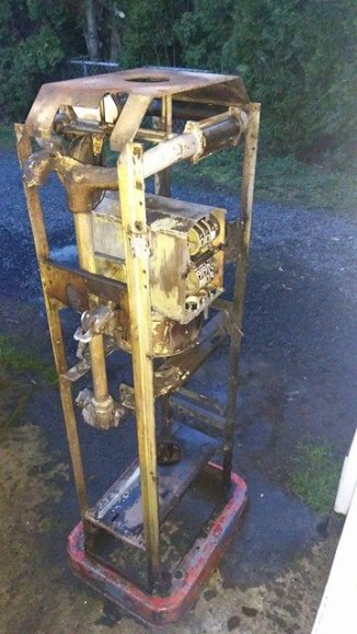 Photograph of a stripped down salvaged vintage Bowser gas pump sitting outside to be cleaned.