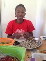 Makilene makes jewelry at Papillon in Haiti