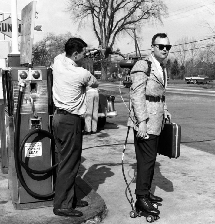 A salesman has his motorized roller skates refueled at a gas station (1961).