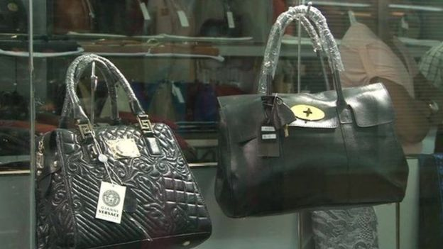 "Would anyone confuse these counterfeit ""Versace"" handbags on sale at a market with the real thing?"