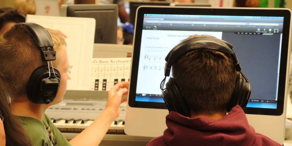 Students writing music on computers for the FAME Composition Project