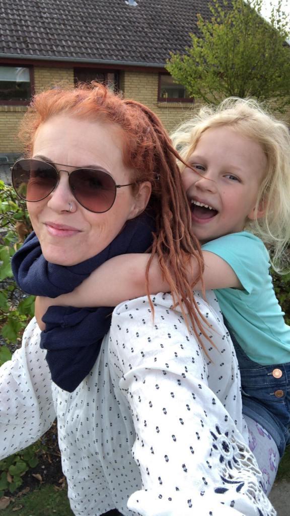 Billede af et barn der bæres på moderent ryg. Barnet griner og moderen har solbriller på.
