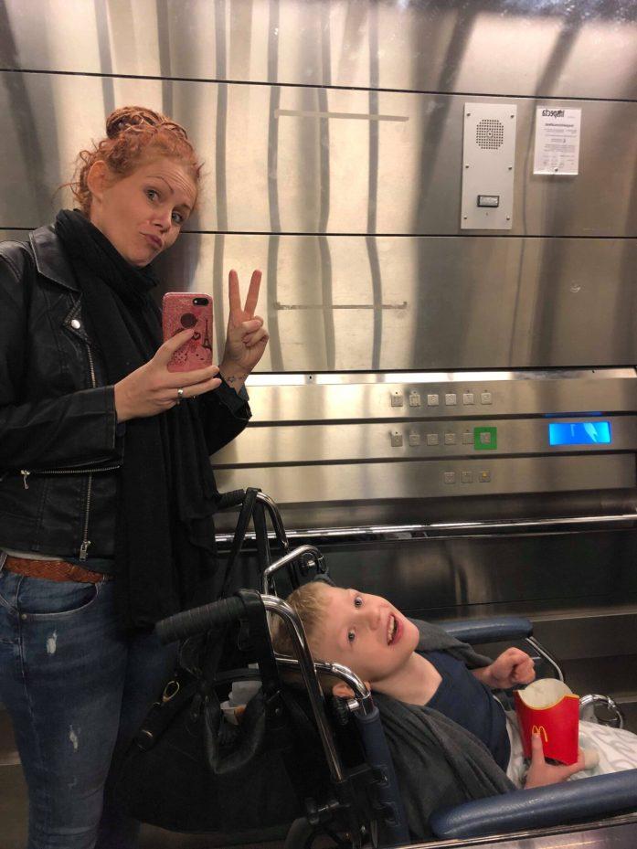 Billede af barn i en kørestol i en elevator. En voksen kvinde står ved siden af og tager et billede ind i elevatorens spejl.