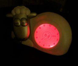 Billede af et ur, udformet som et får der ligger ned. Urskiven er oplyst i rød og fårets øjne er lukkede, for at signalere at det er nat.