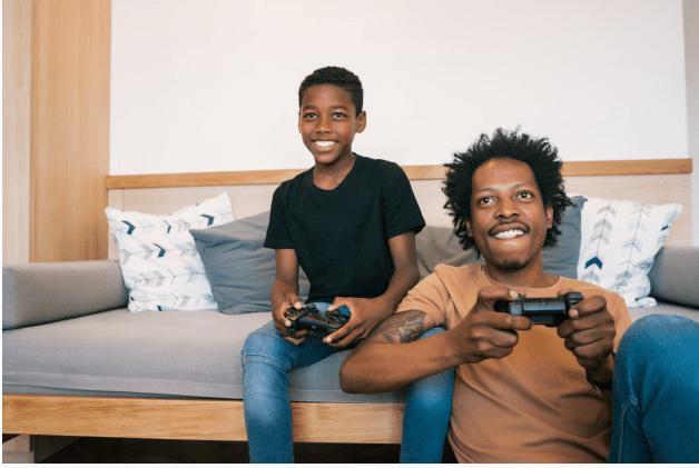 papa africain et son fils qui jouent à la playstation