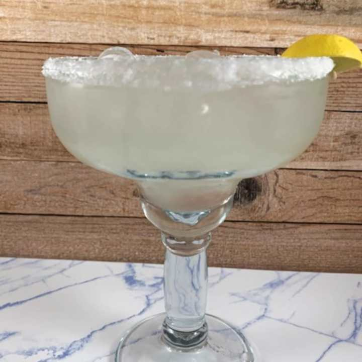 Key lime margarita on a marble surface.